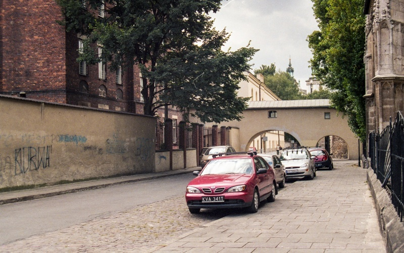 street in prospect, cars in the street, on the left wall, fragment of the building, in the background arcade passage over the street