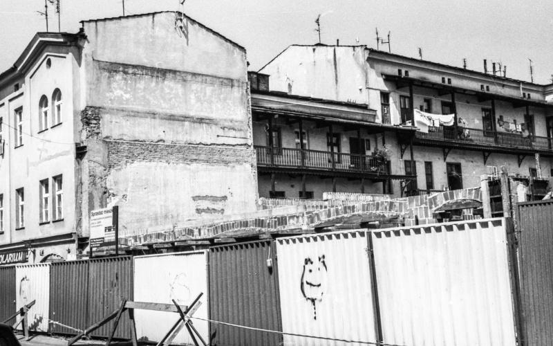 ulica Józefa, ogrodzenie z blachy falistej, z lewej budynek przy ul. Józefa, w głębi oficyny