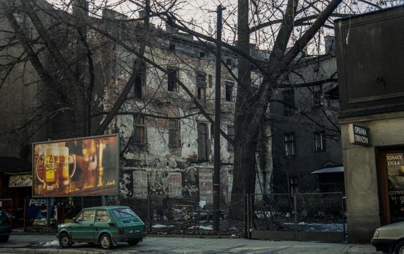 na dole ulica, chodnik - samochód osobowy, z lewej tablica reklamowa, parcela ogrodzona siatką, w środku drzewo, dwupietrowy budynek