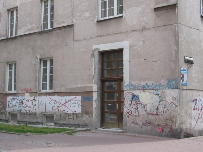 A building at the corner of Wietora and Skawińska streets, football club-related graffitti on the ground floor