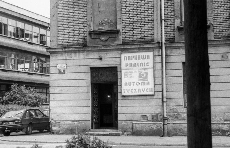 z lewej fragmnet skrzyżowania ulic, samochód osobowy, z prawej słup, fragment ściany frontowej budynku z szyldem reklamowym, otwarte drzwi wejściowe