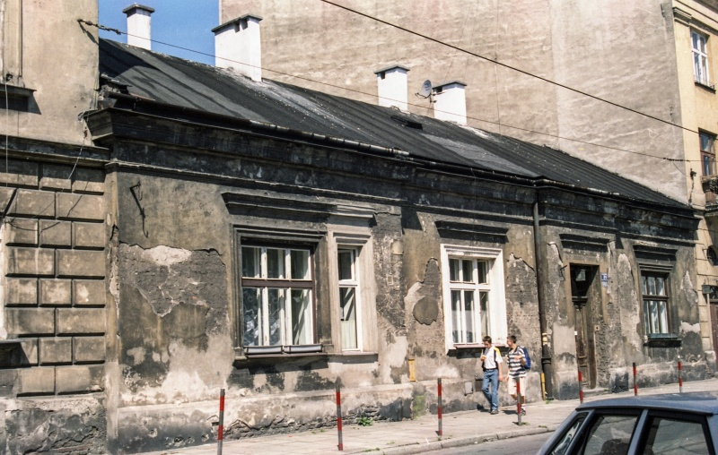 fragment of street, on the right roof of a car, one-storey house