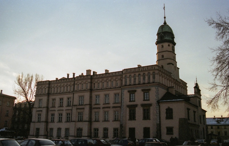 at the bottom roofs of cars, in the centre two-storey building with tower on the right