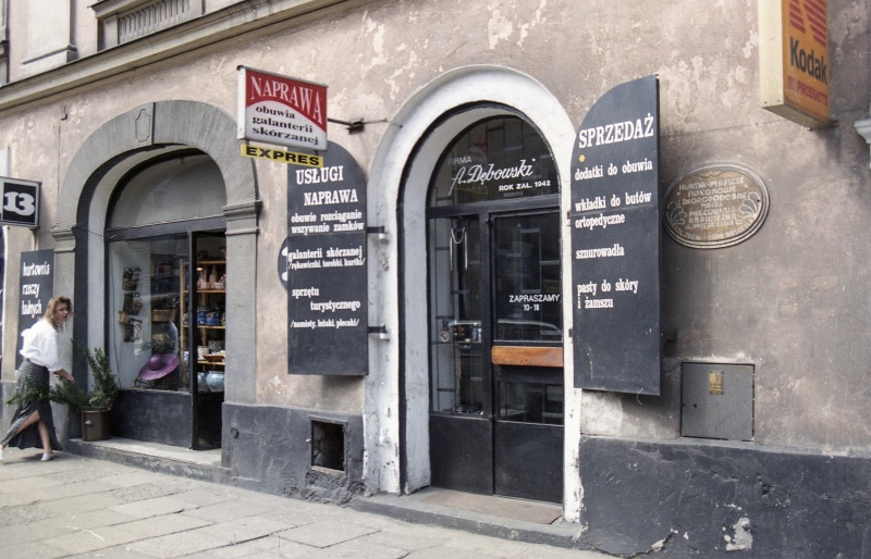 at the bottom street, two shop windows, in the centre a protruding arm with sign