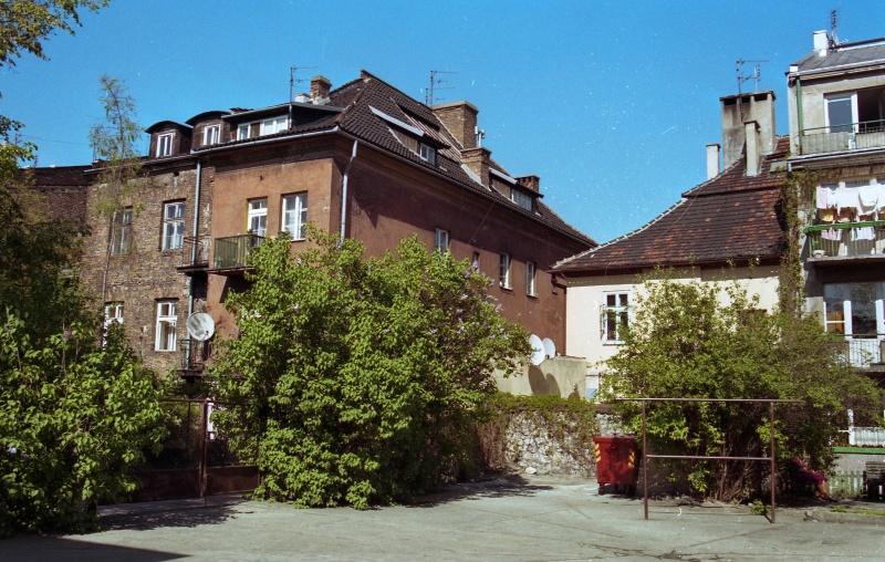 na dole plac z trzepakiem, drzewa, wgłębi kamienice, po lewej budynek prz ul. Ciemnej i narożny budynek przy ul. Szerokiej