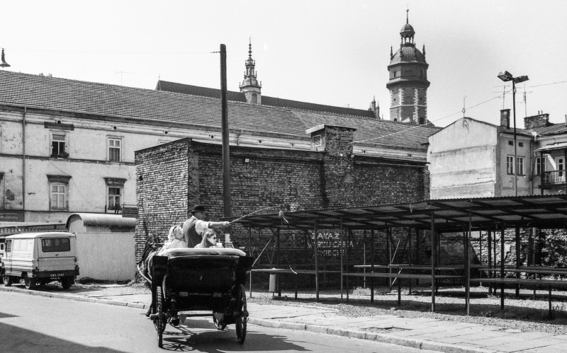 Estery street, hackney carriage, on the right commercial stalls, in the background buildings in Józefa street, tower and roof of Corpus Christi church