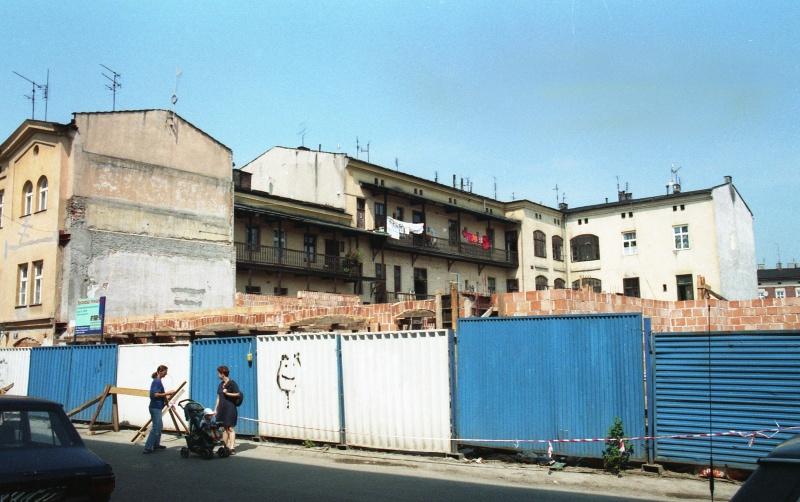 ulica Józefa, ogrodzenie z blachy falistej, z lewej kamienice, w głębi oficyny