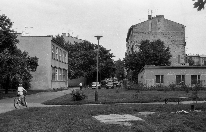 square with grass, tree on the left, a multi-storey building behind it, tenement gable wall on the right in the background