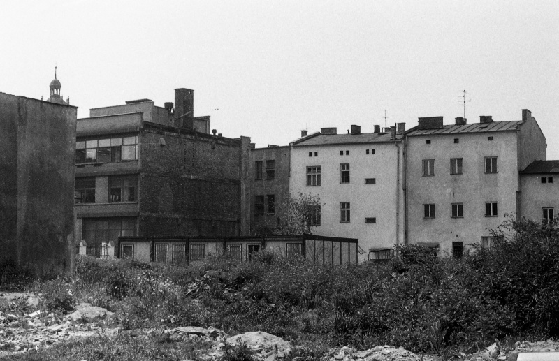 on the left wall of the building, empty plot, rubble and debris, in the background buildings