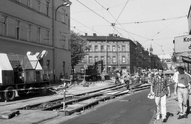 street in prospect, on the right pedestrians on the pavement, on the left repair work on tram tracks, line of tenements in prospect along the street