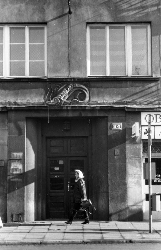 na dole ulica, w środku kobieta, za nią drzwi, nad nimi płaskorzeźba ryby (suma), wużej dwa okna