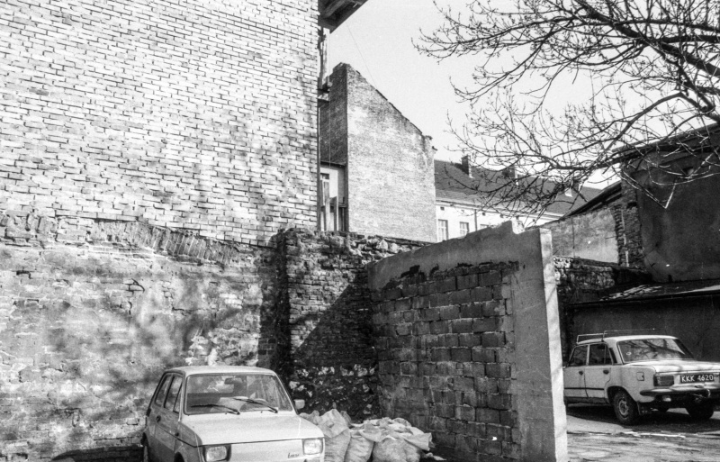 on the left fragment of gable wall with fragment of building wall, car in front, on the right in the background at the bottom car, branches of trees above