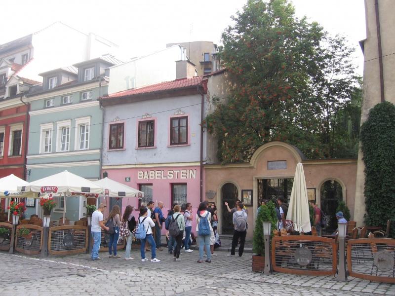 Fragment wschodniej pierzei ul. Szerokiej z grupą turystów przed wejściem na dziedziniec synagogi Poppera