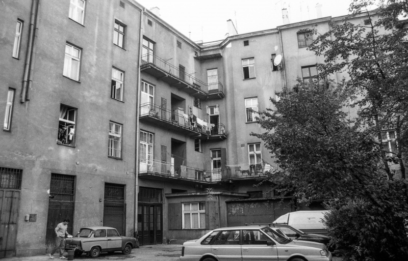 courtyard with cars, on the right tree, tenements
