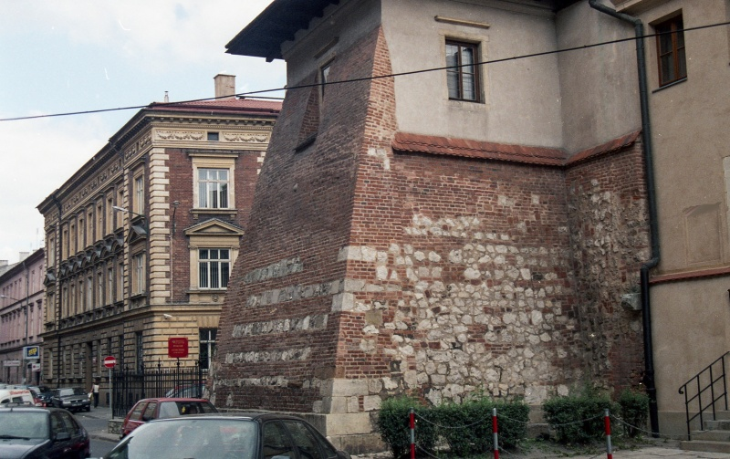 fragment of monastery, on the left cars in the street, in the background tenements