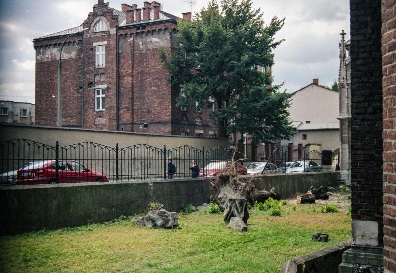 trawnik, z prawej fragment murów kościoła, wgłębi z lewej fasada kamienicy
