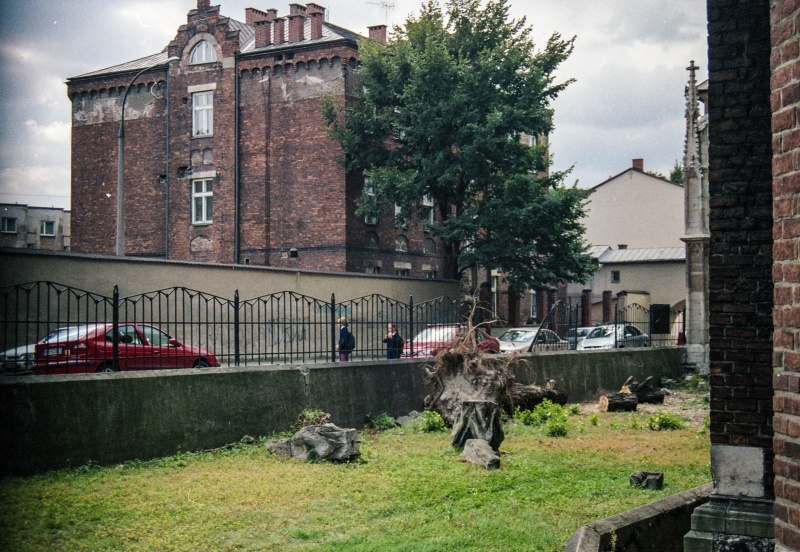 lawn, on the right fragment of church walls, in the background on the left tenement facade