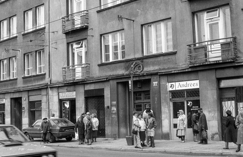 on the left at the bottom car, on the pavement group of people, bottom facades of tenements