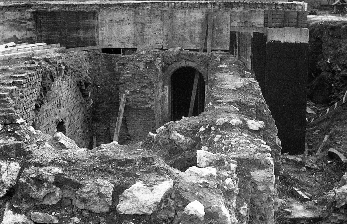 construction site, foundations of a house, masonry arches and vaults, surrounded by dilapidated buildings