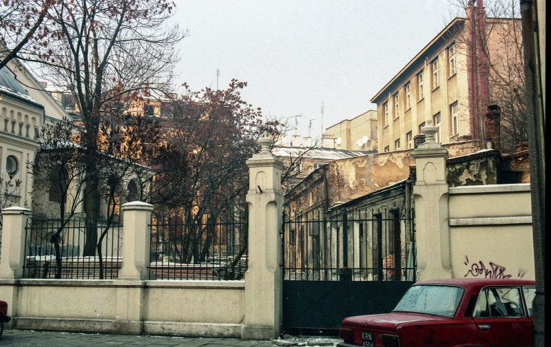 on the right car, metal mesh and poles fence, on the left trees and fragment of synagogue, on the right one-storey annex building by the tenement