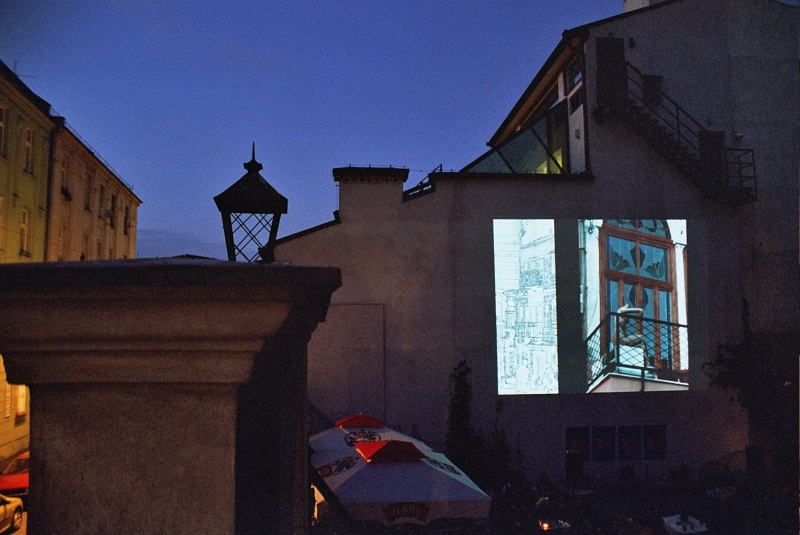 Wall of the building of the Center for Jewish Culture at 17 Meiselsa street, with a slide projected