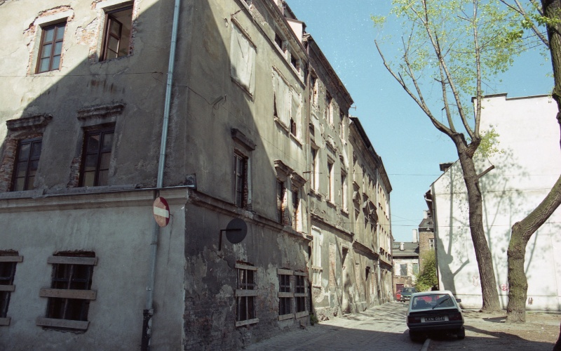 on the left corner building, view of street, on the right car, trees, blank wall of the building