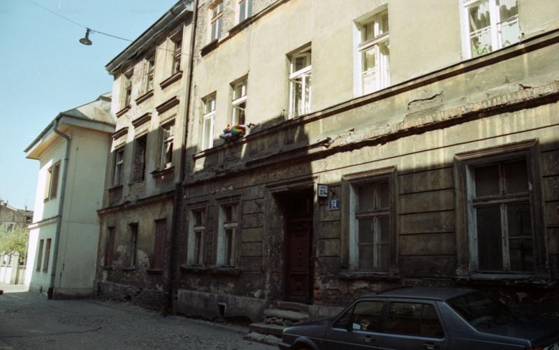 w centrum ulica w perspektywie, z lewej naroże budynku, z prawej ścięty narożnik kamienicy z oknem, na ulicy samochód