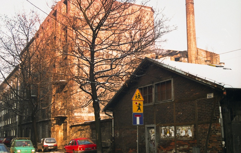 ulica w perspektywie, na dole fragment ul. św. Wawrzyńca, budynek parterowy, nad nim komin, kamienice w zwartej zabudowie