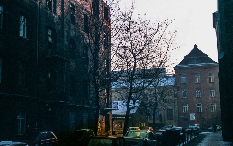 street, one-storey building, chimney above it, in the background tenements