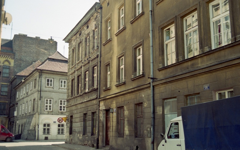 on the left fragment of a street, on the right at the bottom delivery car, front elevations of buildings, in the background buildings, one with stepped roof