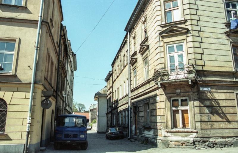 z lewej kamienice, z prawej ulica na której samochód