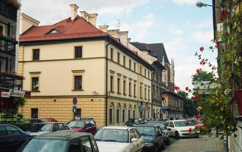 ulica - perspektywa, samochody osobowe, w centrum kamienica dwupiętrowa, wgłębi prezbiterium kościoła