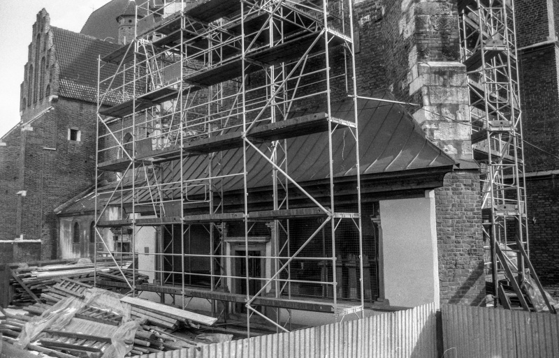 at the bottom corrugated iron fence, pile of boards, bottom floor of building with scaffoldings