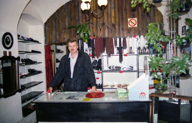 in the centre man behind the counter, commercial part of shop with shelves and wooden wall