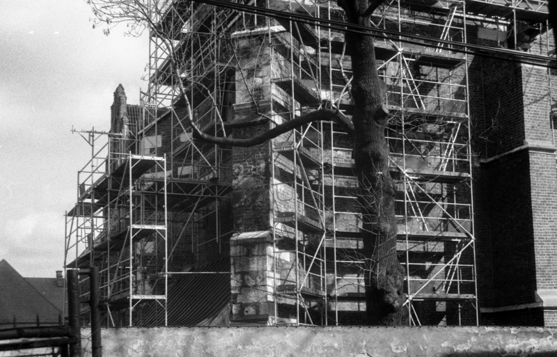 at the bottom street-facing wall, bottom floor of tower covered with scaffoldings, on the right protruding buttress