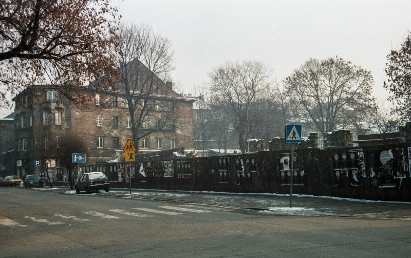 Miodowa street, fence, treetops, in the back on the left three-storey tenement