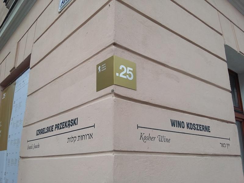 róg budynku przy ulicach Jakuba i Józefa , z napisami i oznaczeniami reklamujacymi 25 festiwal kultury żydowskiej i kawiarni Cheder