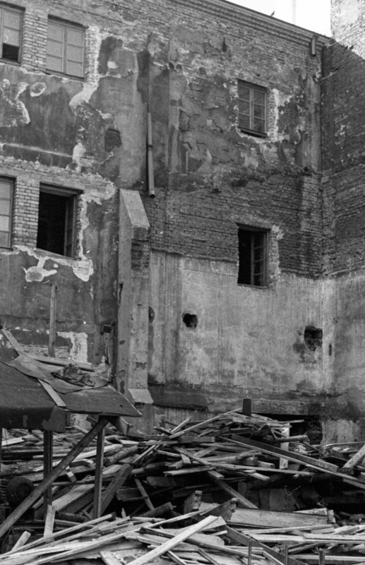 in the foreground boards thrown away at the courtyard, in the background a wall of a two-storey building divided with a buttress