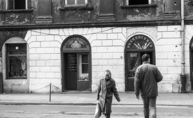 at the bottom street and cars, two people crossing the street, ground floor and first floor of a tenement