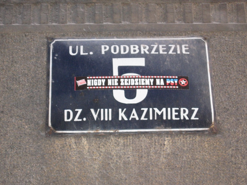 Plaque with a building no. on Podbrzezie street with a football fan sticker of a sports club