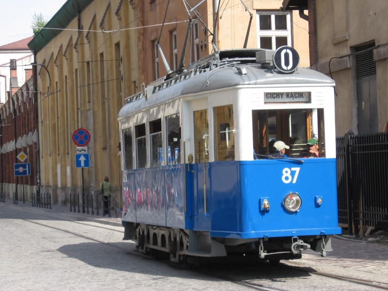 Historic tourist tram on św. Wawrzyńca street, historic power house building in the background
