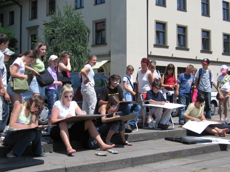 Turyści oglądający studentów rysujących widok na Starą Synagogę