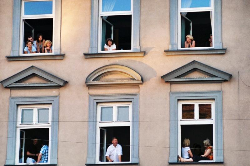 People in windows of a tenement at 30 Szeroka street