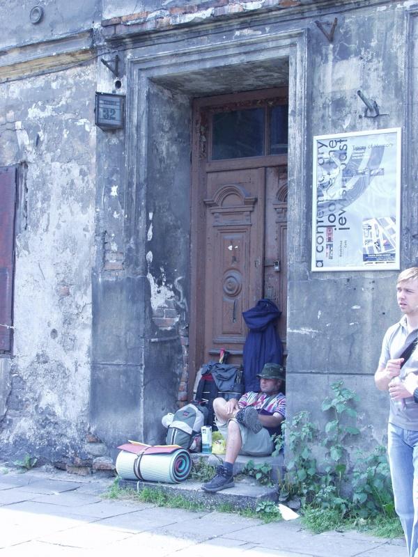 Kamienica na ulicy Szerokiej 32, w bramie odpoczywający turysta