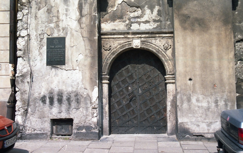 pavement, wall of the building with entrance portal on the right and memorial plate on the left