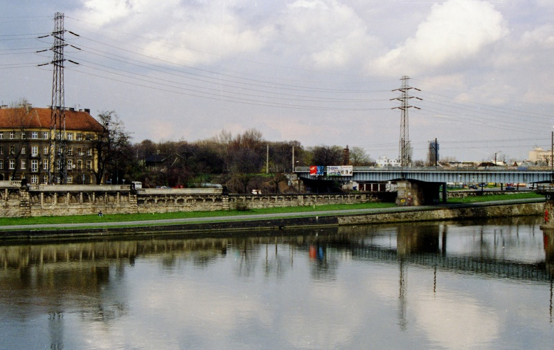 on the left fragment of a river, Vistula boulevard, in the background on the left fragment of a railway bridge, street, trees, buildings