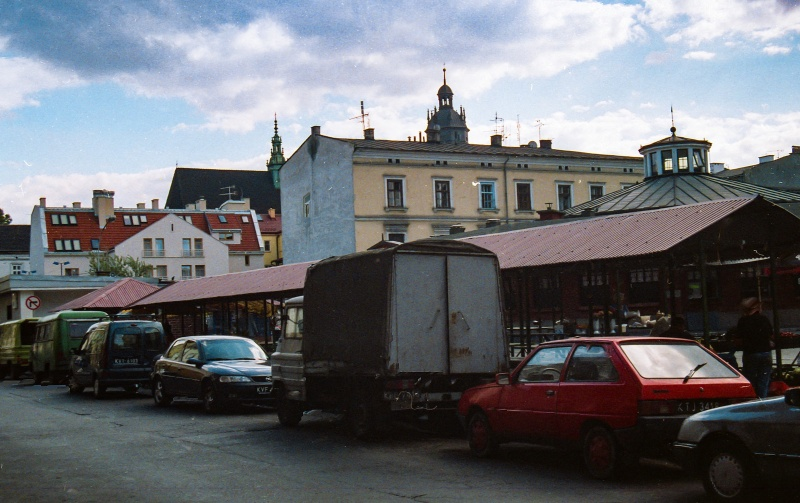 square, car, shopping stalls, in the background roof and tower of Corpus Christi church