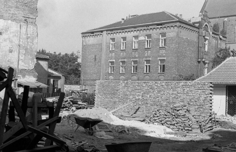 on the left scattered boards, in the background construction site with wheelbarrow, in the back a two-storey building behind a brick wall and part of St. Catherine's church