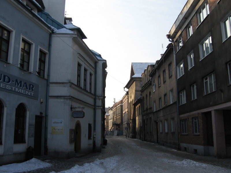 A view of Józefa street with reconstructed buildings on the left hand side an a modernist housing block from communist times on the right