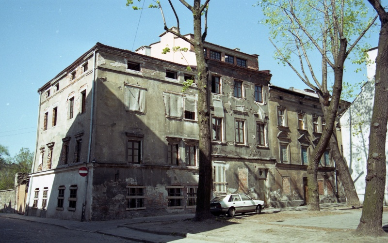 on the left fragment of street, on the right square with trees, front elevations of buildings, on the left corner tenement with Jakuba and Ciemna streets